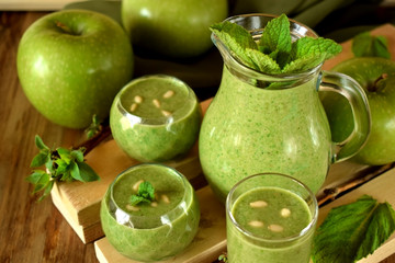 Green smoothie in glass vessels on wooden background