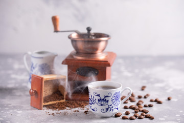 Grains of coffee fall out of a vintage coffee grinder. Hot black coffee in a beautiful porcelain...