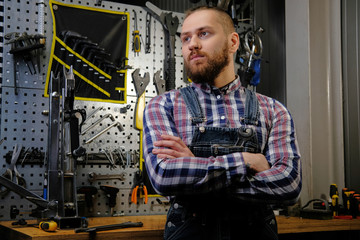 Portrait of a handsome stylish male with beard and haircut wearing a flannel shirt and jeans coverall, standing with crossed arms in a workshop against wall tools.