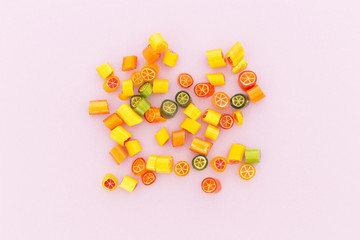 Assortment of colorful sweet handmade candy pieces arranged on light pink paper