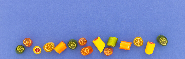 Assortment of colorful sweet handmade candy pieces arranged on blue paper