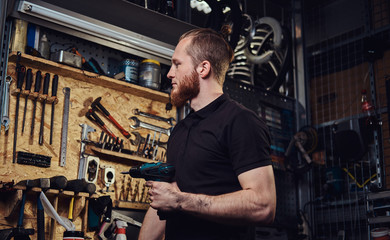 Handsome bearded redhead worker with haircut,  holding an electric screwdriver, working in a repair shop.