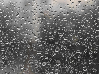Grey rainy day. Drops of rain on the glass. Background