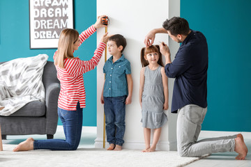 Parents measuring height of their children at home