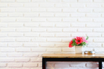 Fake pink and red flower bouquet in white vase on wood table on white brick wall texture background...