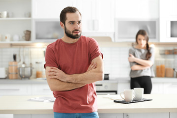 Young couple ignoring each other after having argument in kitchen