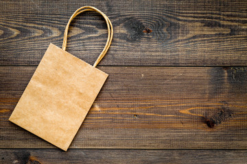 Brown kraft paper bag for shopping on wooden background top view copy space