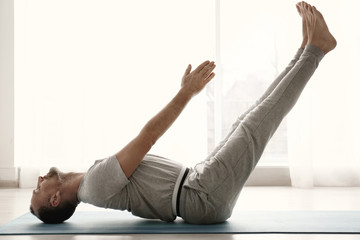 Sporty man practicing yoga indoors