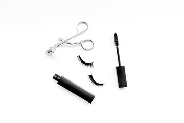 Cosmetics and tools for voluminous lashes. Mascara, false eyelashes, eyelash curler on white background top view space for text