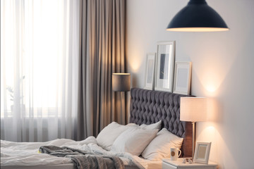 Modern room interior with comfortable bed and stylish lamp