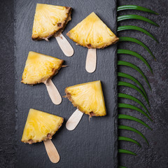 Ripe Pineapple slices on a black background