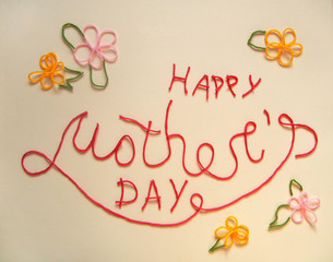 picture of the inscription Happy Mother's day made by red threads on beige background. Hand lettering. Cute text for postcard with flowers.