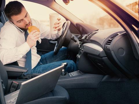 Man eating an hamburger and working seated his car