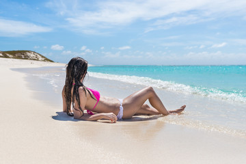 Thin girl on a pink/white bikini laid at the beach on the shore, with waves breaking in. Los Roques archipelago