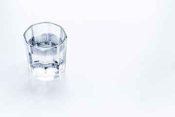 Glass of pure water on white background top view copy space