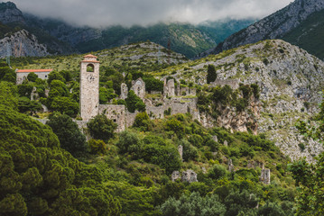 Ancient stone ruins and clock tower at Old Bar town on the cloudy mountains landscape, Montenegro. Stari Bar panoramic view - ruined medieval city on Adriatic coast, Unesco World Heritage Site.