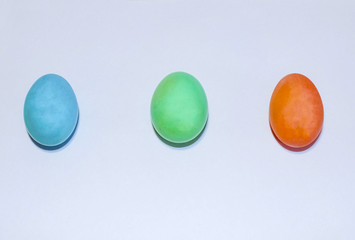 Colored easter eggs three pieces on a white background, minimalism