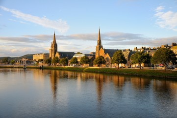 Beautiful Inverness evening cityscape with river view. Two churches are reflected in the water. Inverness, Scotland.