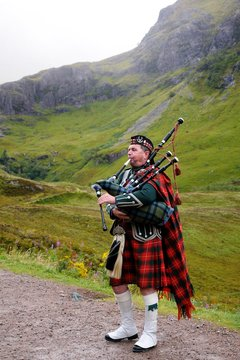 Piper in traditional Scottish outfit plays on bagpipes in Scottish Highlands. In the background of the mountain. Cloudy autumn day.