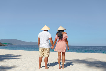 Young beautiful couple in love standing on the beach by the sea and holding hands. Wearing Vietnamese hats. Concept of honeymoon. View from the back.