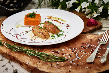 Delicious menu dish meat cutlet with carrot pie on white plate and wooden table