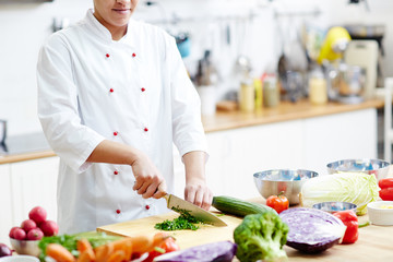 Young chef cutting aromatic herbs for seasoning vegetable salad or soup while cooking at work