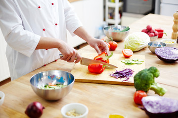 Chef halving fresh red caapsicum on wooden chopping board while cooking vegetable salad for clients