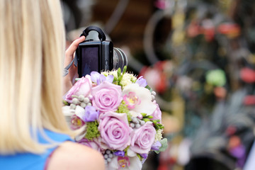 Photographer at the wedding. A girl is taking pictures on a walk. Girl with a camera.