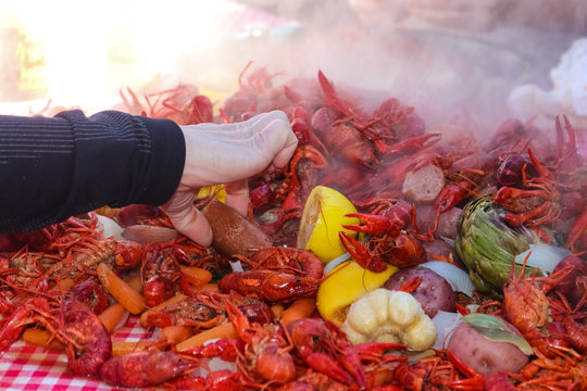 A hand reaching into a pile of steaming food piled on a table at a crawfish boil and grabbing a sausage