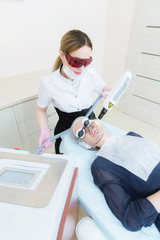 The cosmetician girl in goggles makes the procedure of carbon peeling with the help of a cosmetology laser. Carbon face peeling procedure. Laser pulses clean skin of the face. Hardware cosmetology