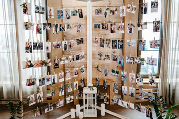Romantic pictures of newlyweds and photos of holiday people hanging on clothesline by clothespins on the stand, garland. wedding decor.