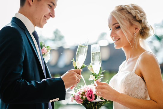 Newlyweds holding glasses of champagne for toast in hands of the outdoor. standing on wedding ceremony under the arch decorated with flowers and greenery in the backyard banquet area.