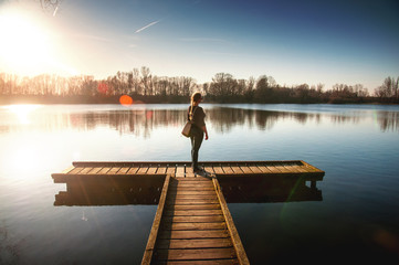 Blonde girl on a wooden landing stage overlooking a lake at sunset in Braunschweig, Germany