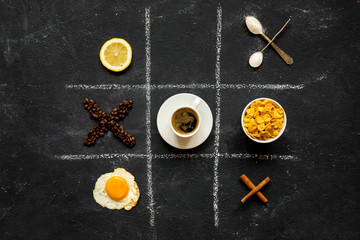Crosses and zeroes from food and objects against a dark background
