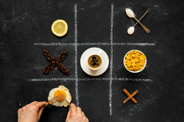 A game a tic-tac-toe from objects and products with the hands cutting the fried eggs
