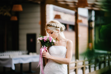 The young beautiful bride in an elegant dress with a bouquet stands at the restaurant at the location for the wedding ceremony.