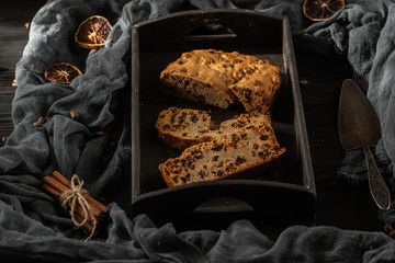 The cake with raisin cut on pieces, against a dark background with a German silver paddle and spices