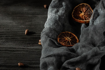 Dried oranges against a dark background with pine nuts