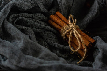 The cinnamon sticks which are tied up by a rope against a dark background