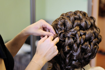 Morning gathering of the bride. The stylist prepares the bride for the wedding. Hair styling.