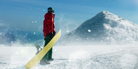 Snowboarder holds board in hands, winter sport