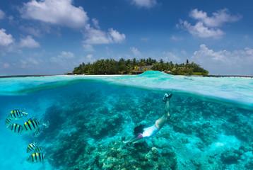 Frau schnorchelt über Korallen und tropischen Fischen vor einer Insel auf den Malediven