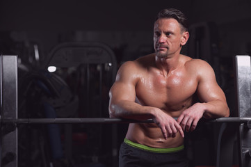 Portrait of a handsome strong male athlete posing shirtless on the background of gym equipment. Mature man showing perfect relief body.