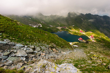area of lake Balea in clouds. Gorgeous summer landscape of Fagarasan mountains, Romania. popular tourist location observed from the top of the ridge