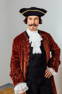 mustachioed eccentric man in the vintage clothes of the baron. Hat tricorn, brown jacket.