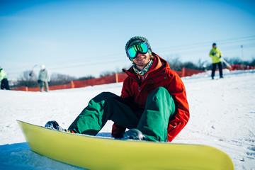 Snowboarder in glasses sitting on snowy slope