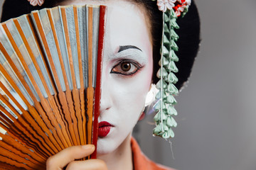 Woman in geisha makeup and a traditional Japanese kimono. Studio, Indoor.