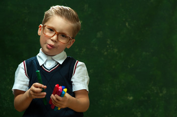 Cheerful little boy in glasses with fashionable styling in formal attire looks into the camera saying something and holding pens on dark green background