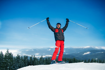 Male skier hands up on the top of mountain