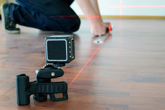Man using cross-line laser to mark the floor. Focus on laser. Room for text.